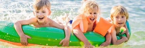Les enfants nagent en mer sur un matelas gonflable et ont la BANNIÈRE d'amusement, LONG FORMAT images libres de droits