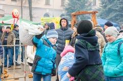 Les enfants non définis avec des sacs combattent sur le rondin pendant la célébration de Maslenitsa dans la ville de Bryansk Image stock
