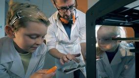 Les enfants observent de près un détail imprimé dans 3D avec un instructeur de laboratoire banque de vidéos