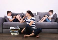 Les enfants observent les comprimés et leur mère essaye de les lire livre Photographie stock libre de droits