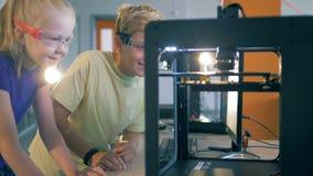 Les enfants observent un processus de l'impression 3D banque de vidéos