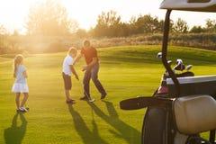 Les enfants occasionnels à un golf mettent en place tenir des clubs de golf studing avec le trai photographie stock libre de droits
