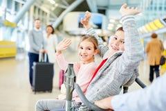 Les enfants ondulent au revoir dans le terminal photographie stock libre de droits
