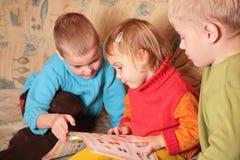 Les enfants ont affiché le livre sur le sofa Images stock