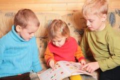 Les enfants ont affiché le livre sur le sofa Image stock