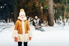 Les enfants ont l'amusement dans la forêt de pein complètement de neige dans un jour d'hiver Photo stock