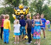 Les enfants ont l'amusement et jouent avec l'animateur dans le bourdon de transformateur de costume Photographie stock