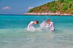 Les enfants ont l'amusement jouant en mer sur le fond bleu L'eau d'éclaboussure de garçons sur l'un l'autre Concept des vacances  Images libres de droits
