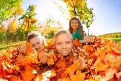 Les enfants ont l'amusement s'étendant au sol avec des feuilles Photos stock