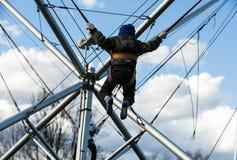 Les enfants ont l'amusement sautant sur le trempoline de bungee fixé avec les bandes élastiques Photos libres de droits
