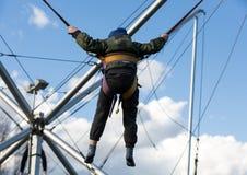 Les enfants ont l'amusement sautant sur le trempoline de bungee fixé avec les bandes élastiques Photo stock