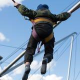 Les enfants ont l'amusement sautant sur le trempoline de bungee fixé avec les bandes élastiques Images stock