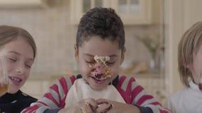 Les enfants ont l'amusement se reposant ensemble à la table Il y a le gâteau enduit sur le visage de garçon, gâteau de malaxa banque de vidéos