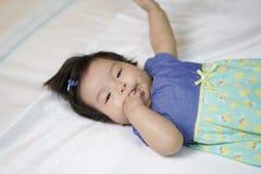 Les enfants ont mis un doigt dans sa bouche pour dormir sur le divan, blanc images stock