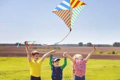 Les enfants ont plaisir à jouer avec un cerf-volant de vol dans le pré le jour ensoleillé Photographie stock libre de droits