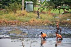 Les enfants pêchent des poissons dans la boue de l'étang à la campagne Nonthaburi Thaïlande Photographie stock libre de droits