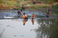 Les enfants pêchent des poissons dans la boue de l'étang à la campagne Nonthaburi Thaïlande Image libre de droits
