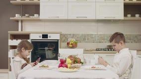 Les enfants parlent à la table avant un dîner de famille banque de vidéos