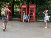 Les enfants posent pour le père par les cabines téléphoniques rouges traditionnelles, Lo Photo libre de droits