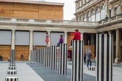 Les enfants posent sur des dessus de colonne chez Colonnes de Buren, Palais Royal, Photos stock