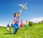 Les enfants positifs et le garçon courants tenant l'avion jouent Photographie stock libre de droits