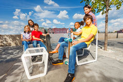 Les enfants positifs s'asseyent sur les chaises blanches avec des planches à roulettes Image stock