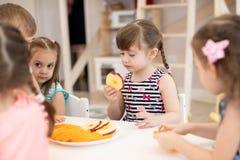 Les enfants prennent le déjeuner au service de garderie Enfants mangeant des fruits frais dans le jardin d'enfants image stock