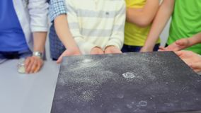 Les enfants regarde le plat de Chladni avec le sable de danse