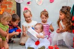 Les enfants regardent des boîtes avec des cadeaux Les vacances des enfants Photo stock