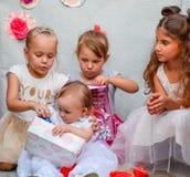 Les enfants regardent des boîtes avec des cadeaux Les vacances des enfants Photographie stock libre de droits