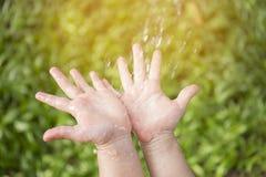 Les enfants remettent avec des baisses de l'eau dessus Photos stock