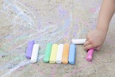 Les enfants remettent avec la craie colorée sur l'asphalte Images stock