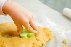 Les enfants remettent avec la forme de biscuits de Noël pour des enfants, faisant le pain d'épice sous la forme de l'homme Festin photos libres de droits