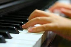Les enfants remettent sur la clé de piano Image libre de droits