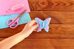 Les enfants remettent tenir un papillon de feutre Le feutre couvre, des ciseaux, fil, perles Fond en bois de Brown avec l'espace  Photo stock