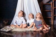 Les enfants reposant ensemble des soeurs de frères de filles de garçons que les yeux bleus de regard après reposent le plancher b photos stock