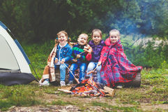 Les enfants rient et font frire des saucisses à l'enjeu près de la tente Photo libre de droits