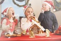 Les enfants s'approchent de la maison de pain d'épice Image stock