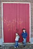 Les enfants s'approchent de la trappe en bois rouge image libre de droits