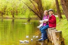 Les enfants s'asseyants près de l'étang jouent avec les bateaux de papier Image stock