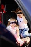 Les enfants s'asseyent dans la voiture et jouent Photographie stock