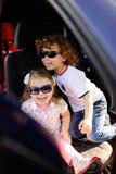 Les enfants s'asseyent dans la voiture et jouent Images stock