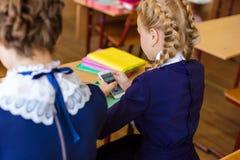 Les enfants s'asseyent dans les téléphones aux leçons Photographie stock libre de droits
