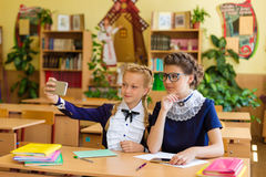 Les enfants s'asseyent dans les téléphones aux leçons Photo stock