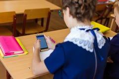 Les enfants s'asseyent dans les téléphones aux leçons Photos libres de droits