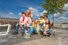 Les enfants s'asseyent ensemble sur des chaises avec des planches à roulettes Image stock