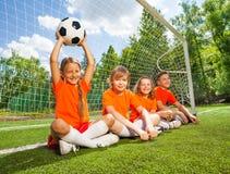 Les enfants s'asseyent ensemble sur le champ avec le football photo libre de droits