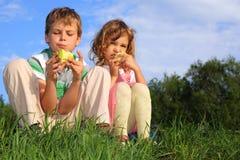 Les enfants s'asseyent sur l'herbe et mangent des pommes. Image libre de droits