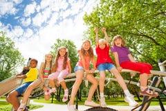 Les enfants s'asseyent sur la barre ronde de la construction de terrain de jeu Photographie stock