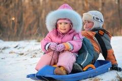 Les enfants s'assied sur le traîneau en plastique Photos libres de droits